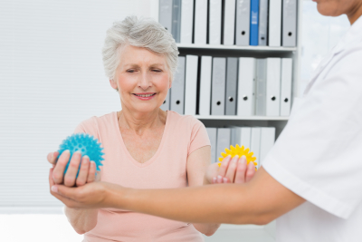 cropped doctor with senior patient using stress buster balls at the medical office