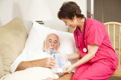 home health nurse helps a senior patient with his respiratory therapy