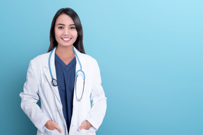 Smiling asian woman physician in a white coat over blue background