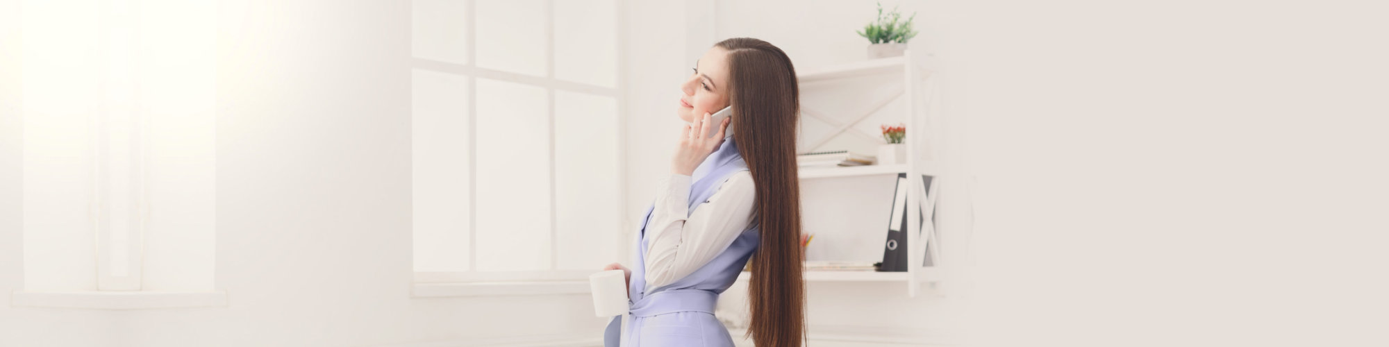 Smiling business woman talking by phone near window at office workplace, copy space.