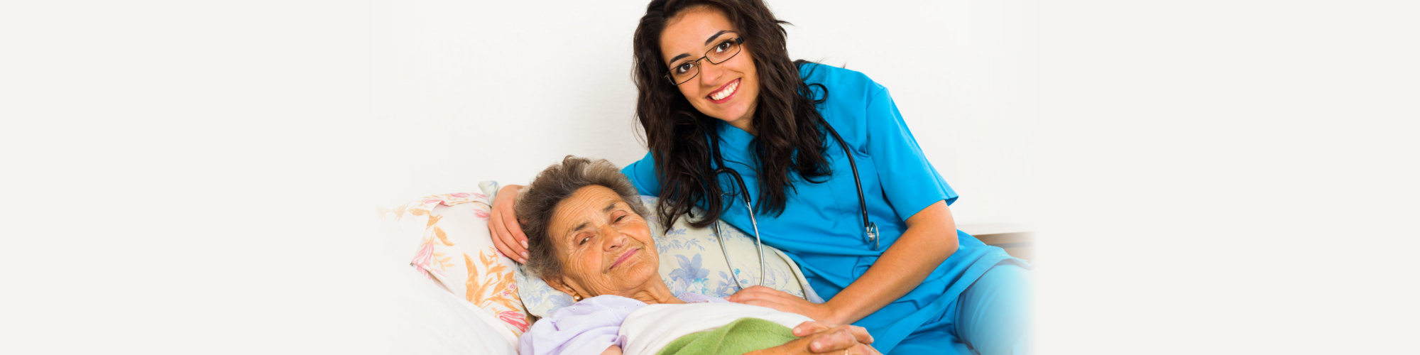 Smiling nurse caring for kind elder patient in nursing home
