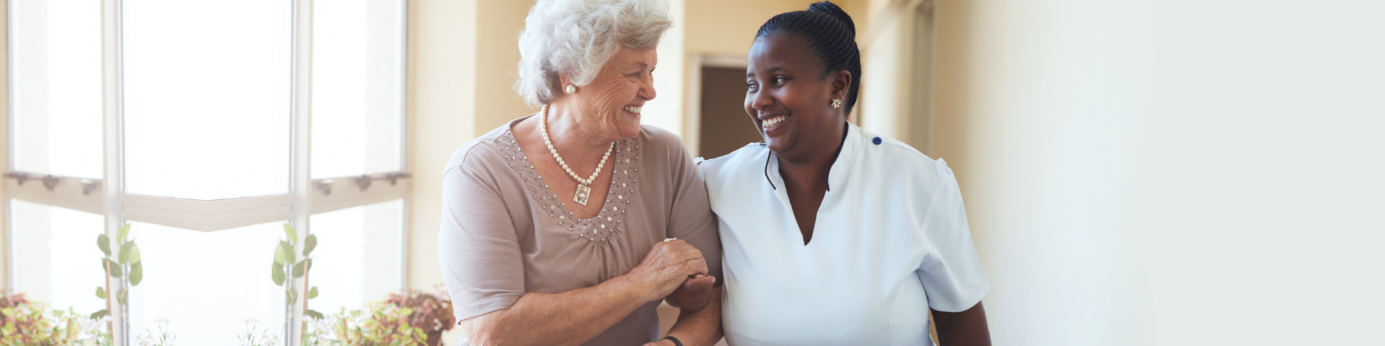 Portrait of smiling home caregiver and senior woman walking together through a corridor